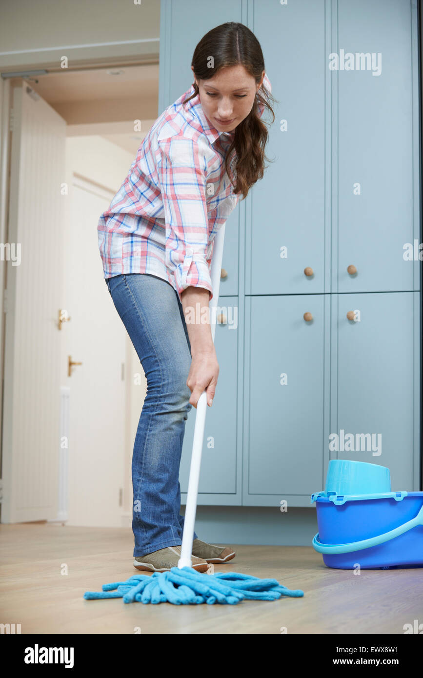 Woman Cleaning Kitchen Floor With Mop - Stock Image