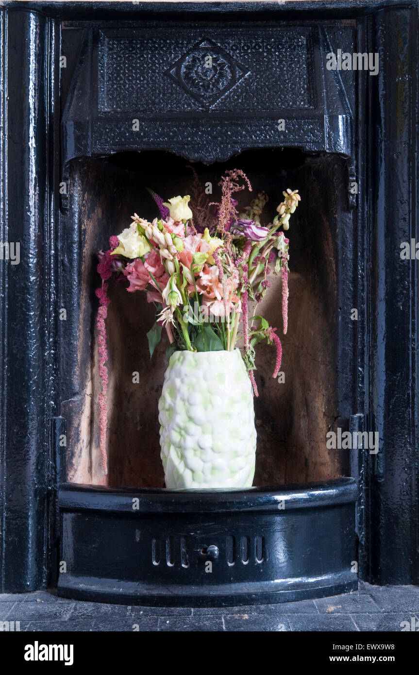 A vase of flowers sitting in a black cast iron fireplace - Stock Image