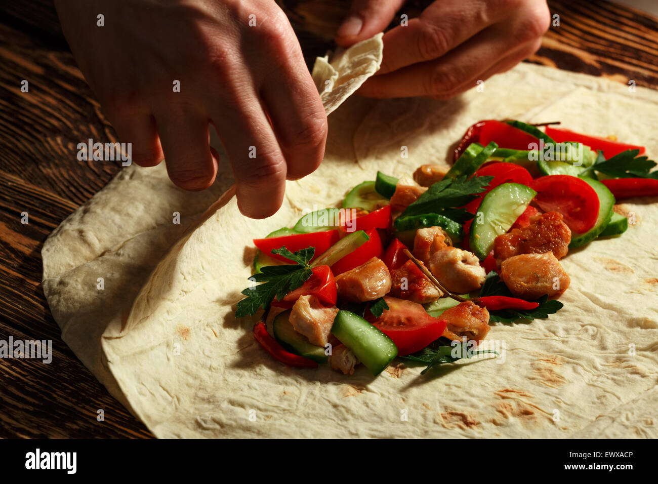 Cooking traditional shawarma wrap with chicken and vegetables - Stock Image