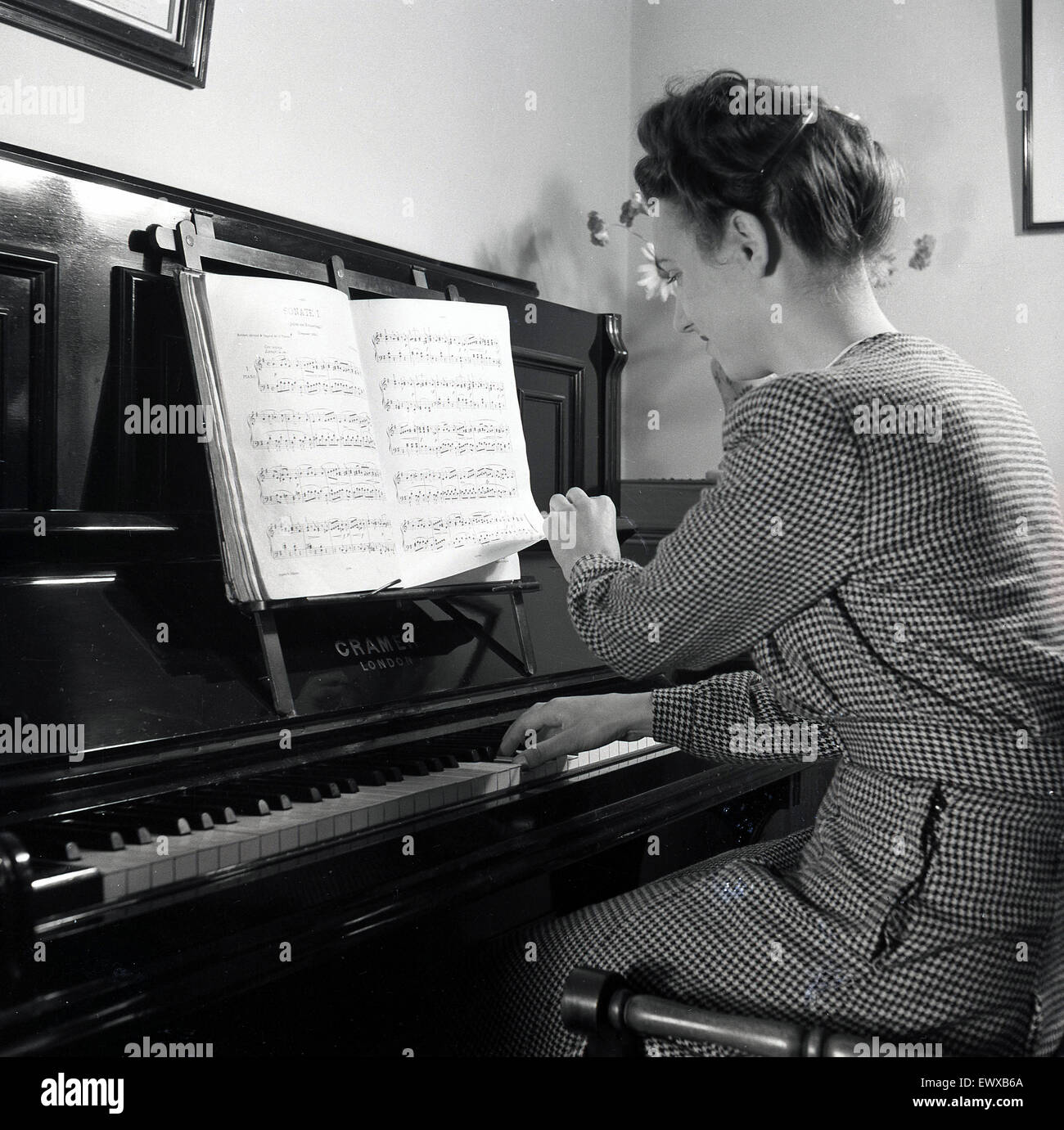 1950s, England. Lady practising on the piano at home in this historical photograph by J Allan Cash. - Stock Image