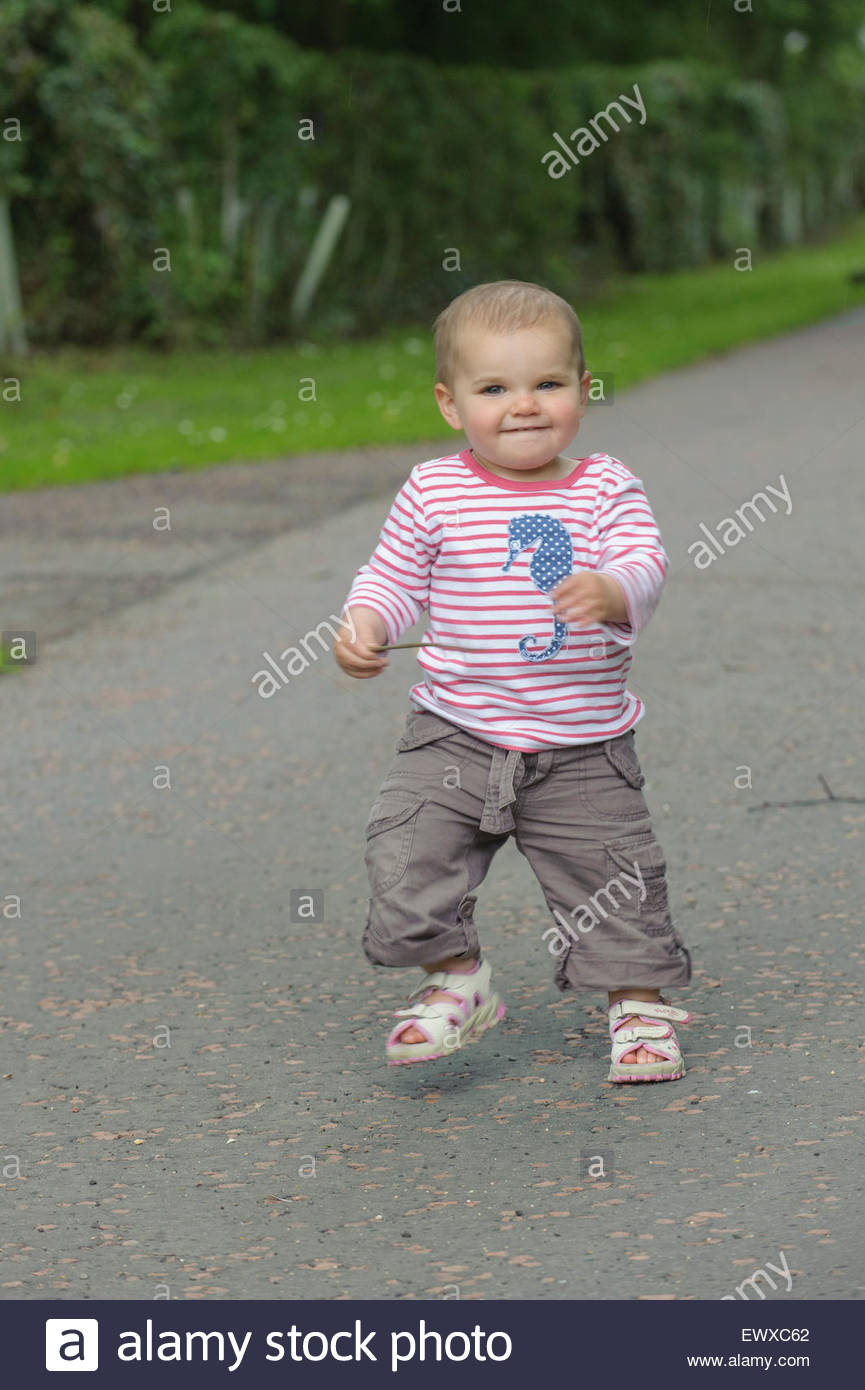 Young child toddling down a path - Stock Image