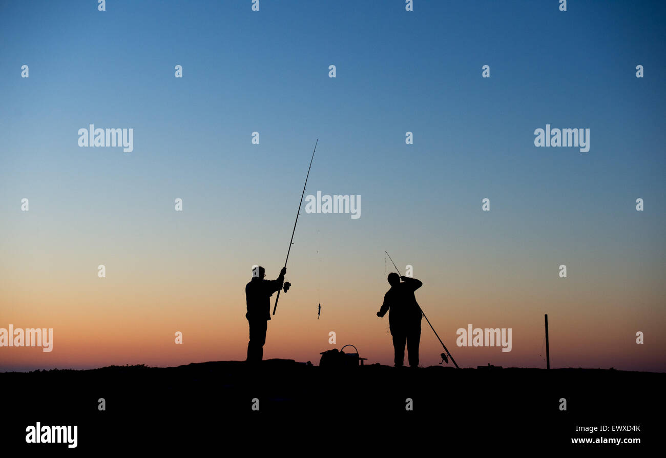 Two fisherman stand against the evening sky at the mouth of the habour in the southern coastal town Simrishamn, - Stock Image