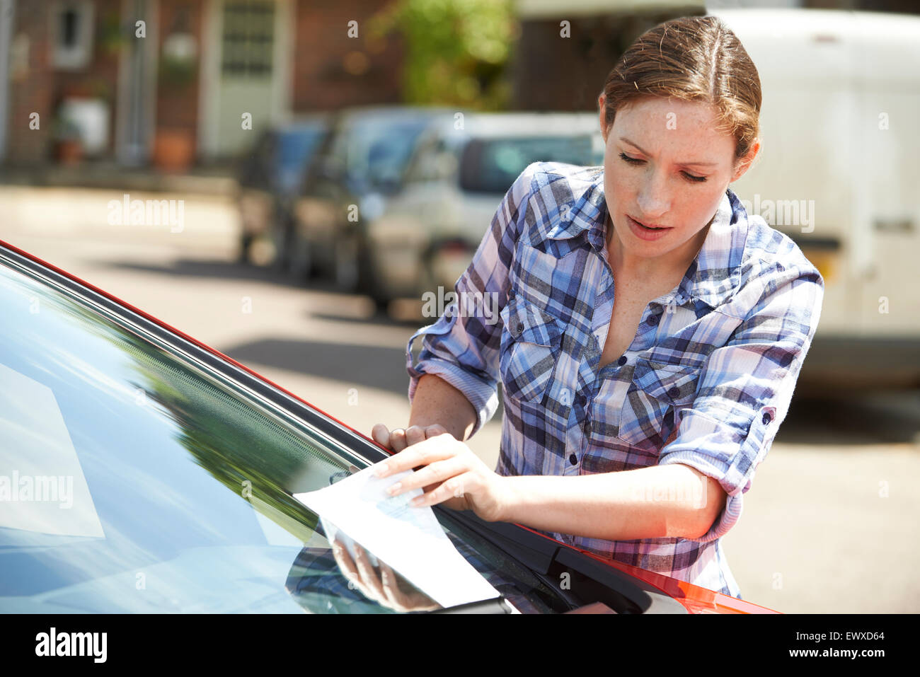 Frustrated Female Motorist Looking At Parking Ticket - Stock Image