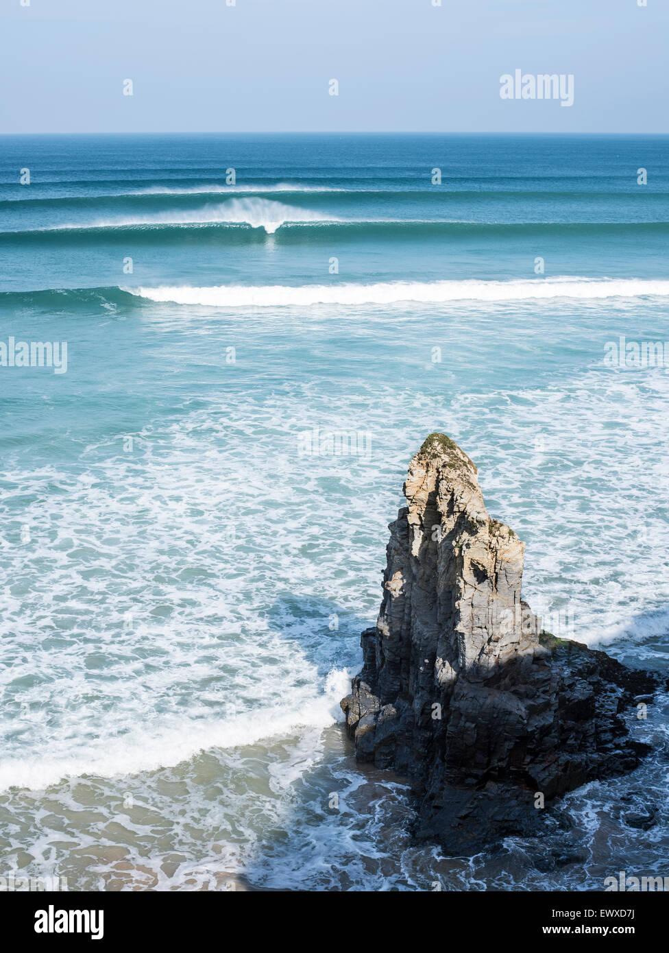 Empty clean surfing waves breaking at Gwithian in Cornwall, with clear blue skies and coastal rock. - Stock Image