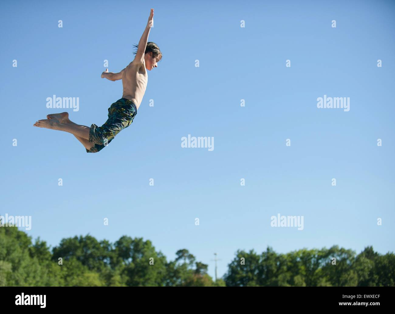 Berlin, Germany. 1st July, 2015. A young man jumps from a jetty into the cold and refreshing water of the 'Flughafensee' - Stock Image