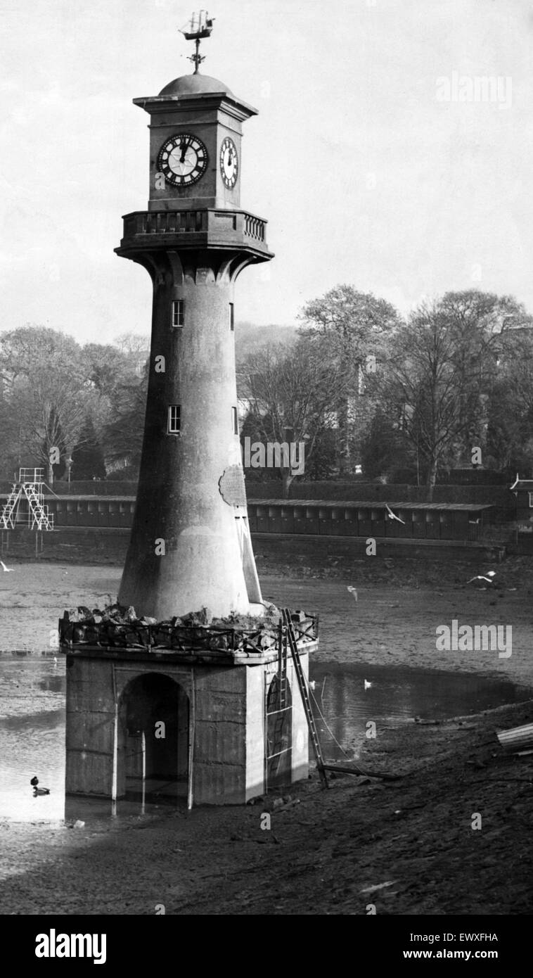 The water has been drained from Roath Park Lake for winter cleaning. Pictured is the lighthouse memorial in the - Stock Image