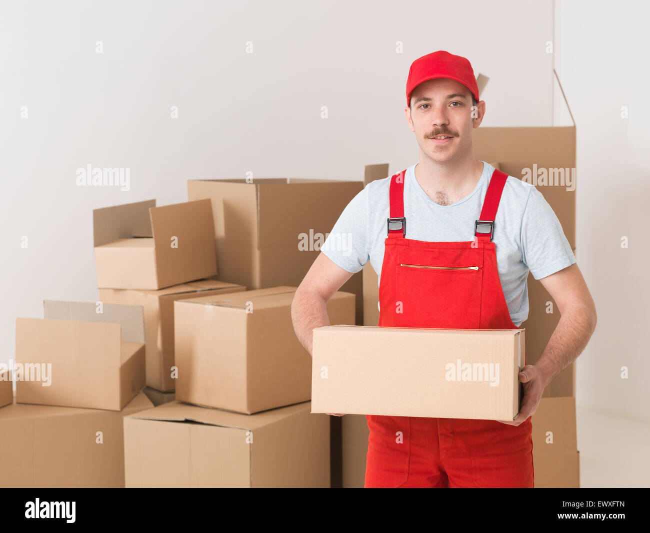 young caucasian deliveryman standing in warehouse, holding parcel - Stock Image