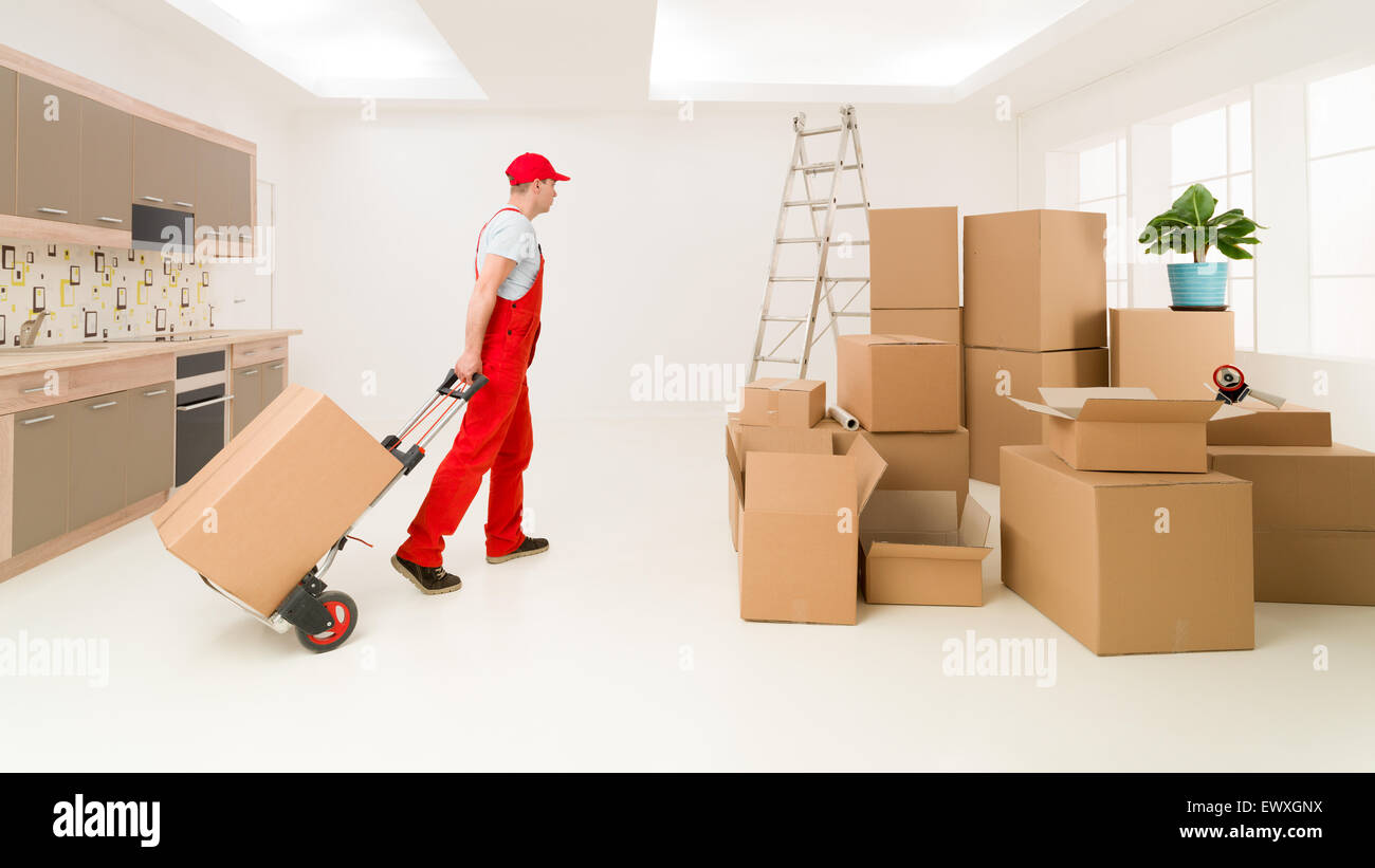 caucasian deliveryman in red uniform holding hand truck, delivering boxes to new house - Stock Image
