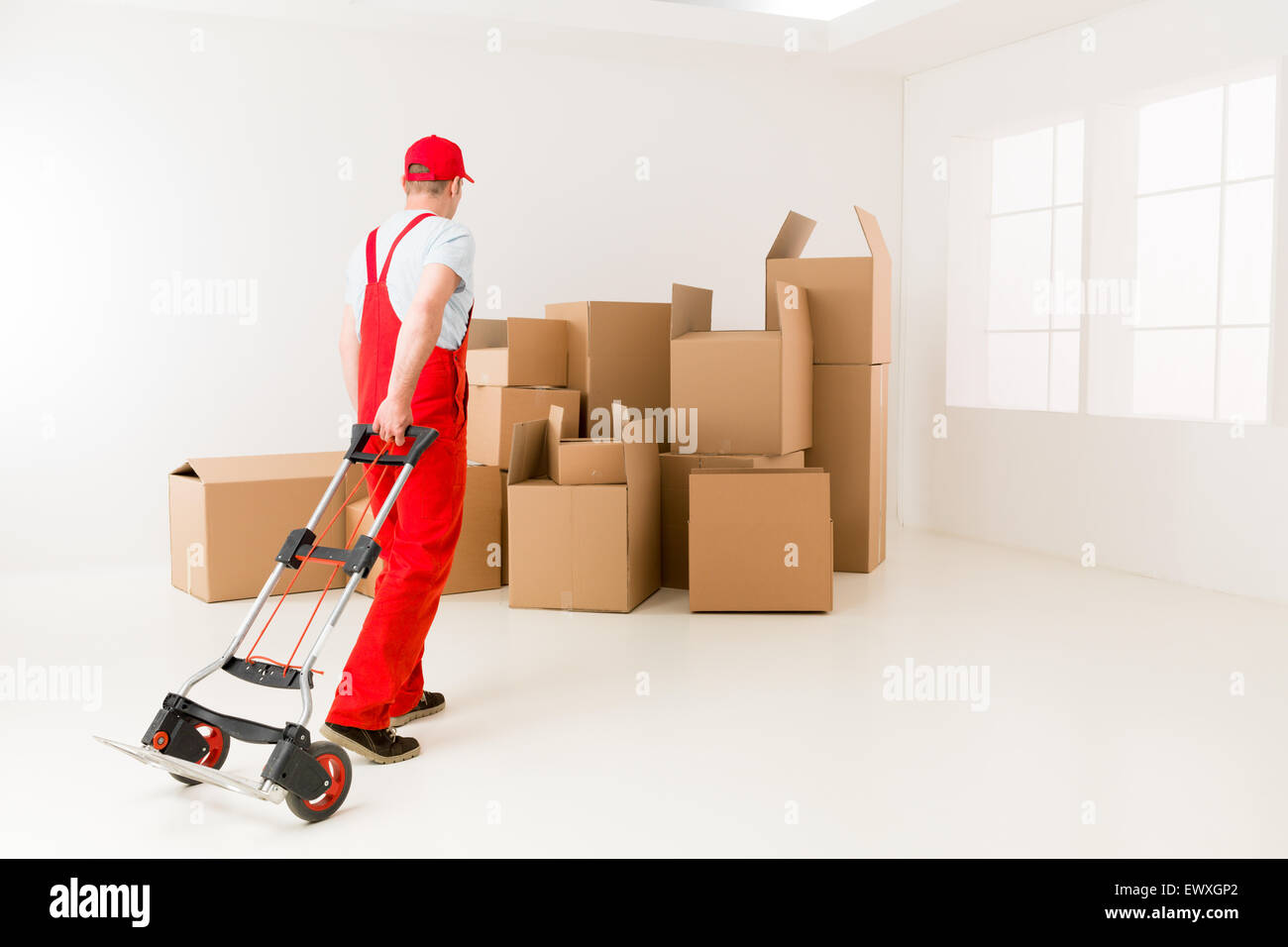 caucasian deliveryman in red uniform holding hand truck, getting ready to load cardboard boxes - Stock Image