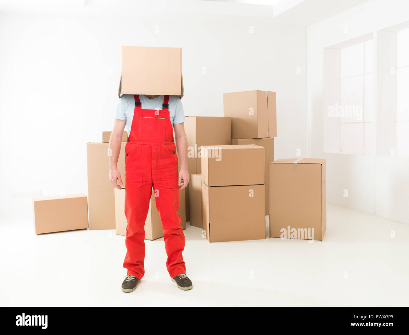 front view of deliveryman standing in new house with box covering his head. copy space available - Stock Image