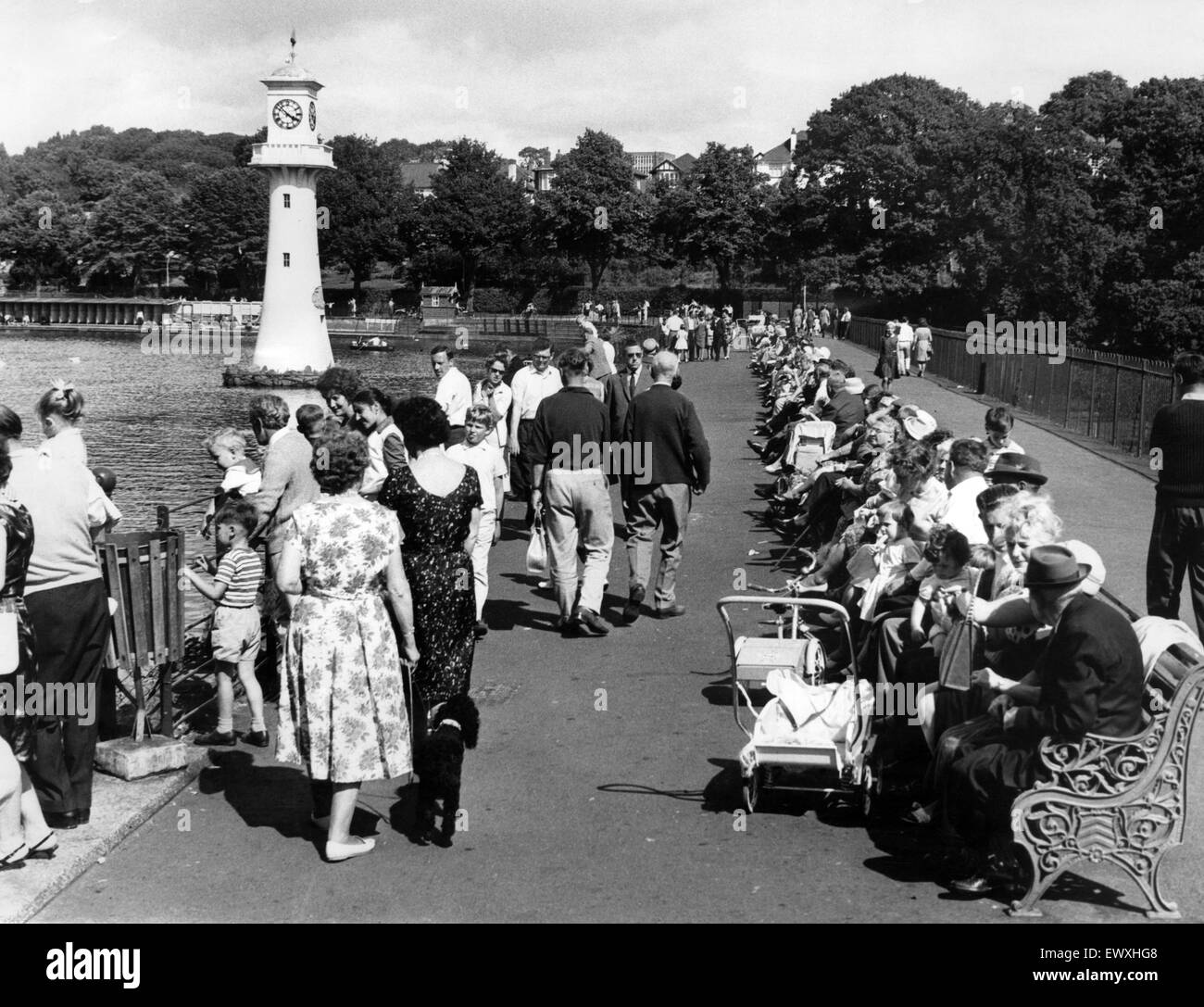 People enjoying an afternoon's sunshine on Roath Park Lake. Pictured in the background is the lighthouse memorial - Stock Image