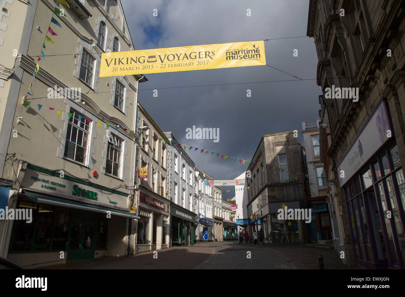 Threatening grey rain clouds over town centre street, Falmouth, Cornwall, England Viking Voyagers advertising banner - Stock Image