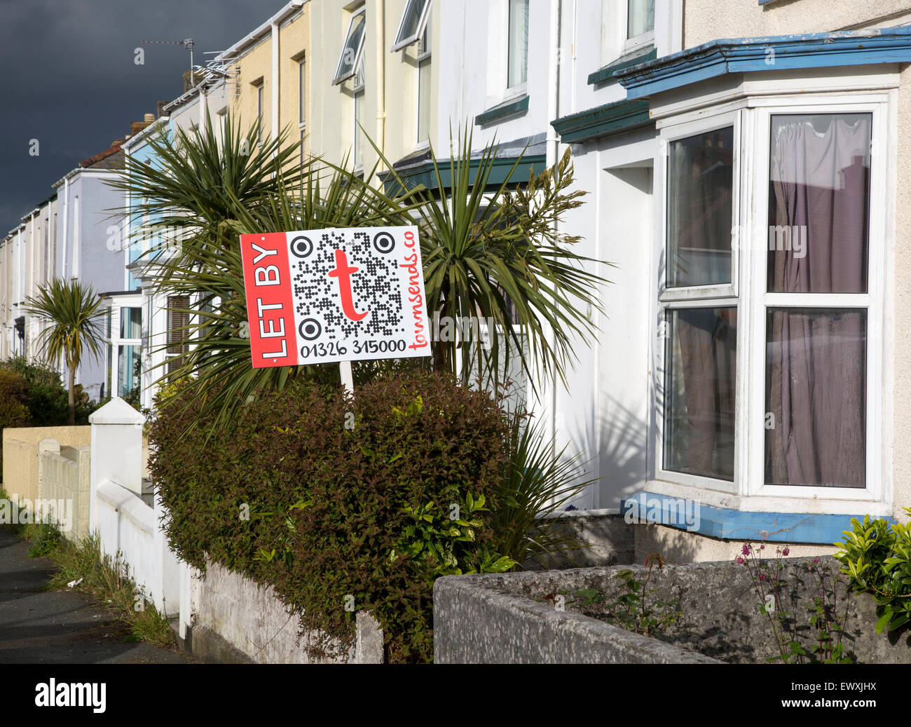 Terraced housing with letting signs  in Falmouth, Cornwall, England, UK with storm clouds overhead - Stock Image