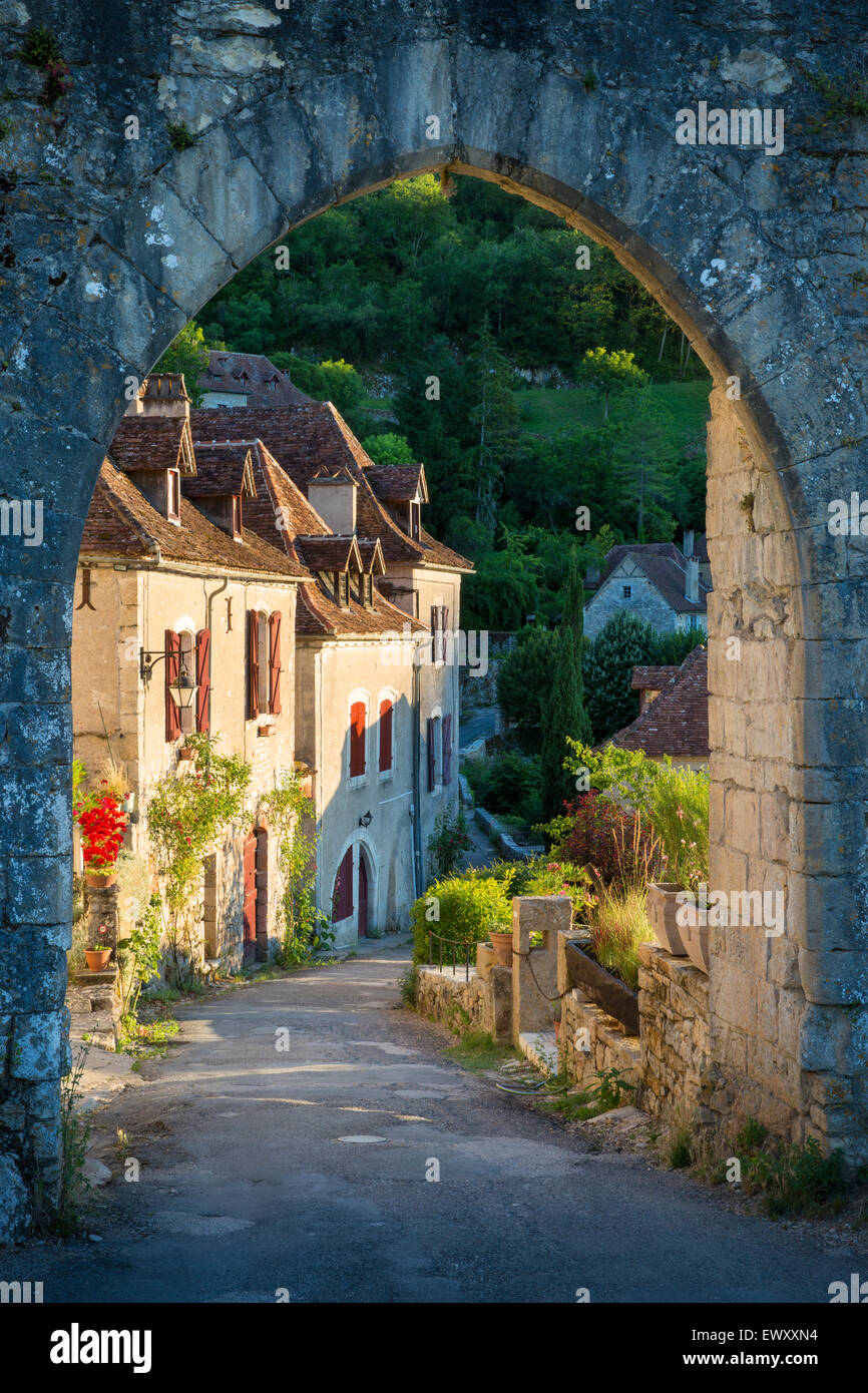 Setting sunlight on homes at entry gate to Saint-Cirq-Lapopie, Lot Valley, Midi-Pyrenees, France - Stock Image