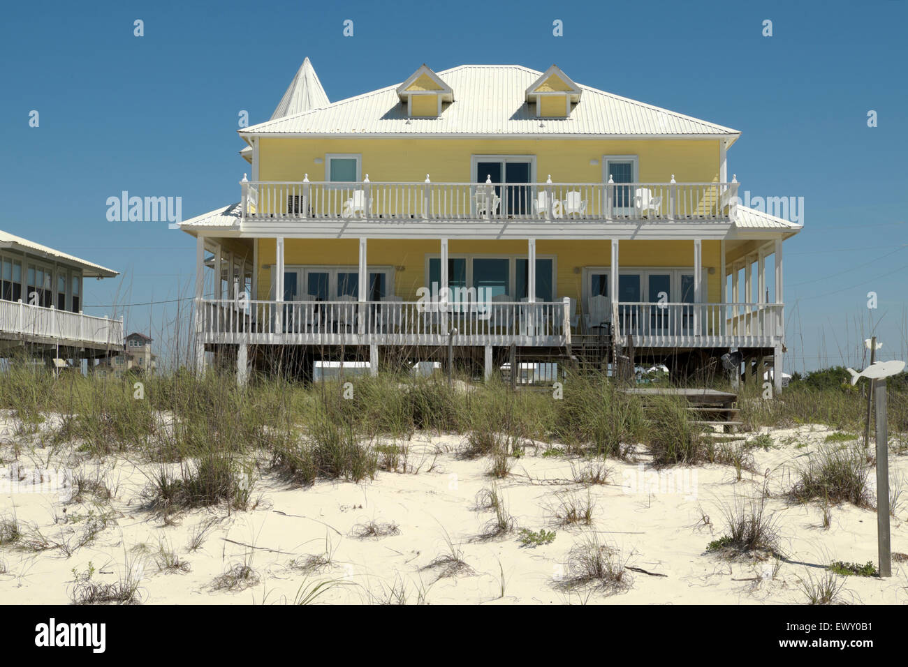 yellow beach house sits near the gulf of mexico beach about twenty