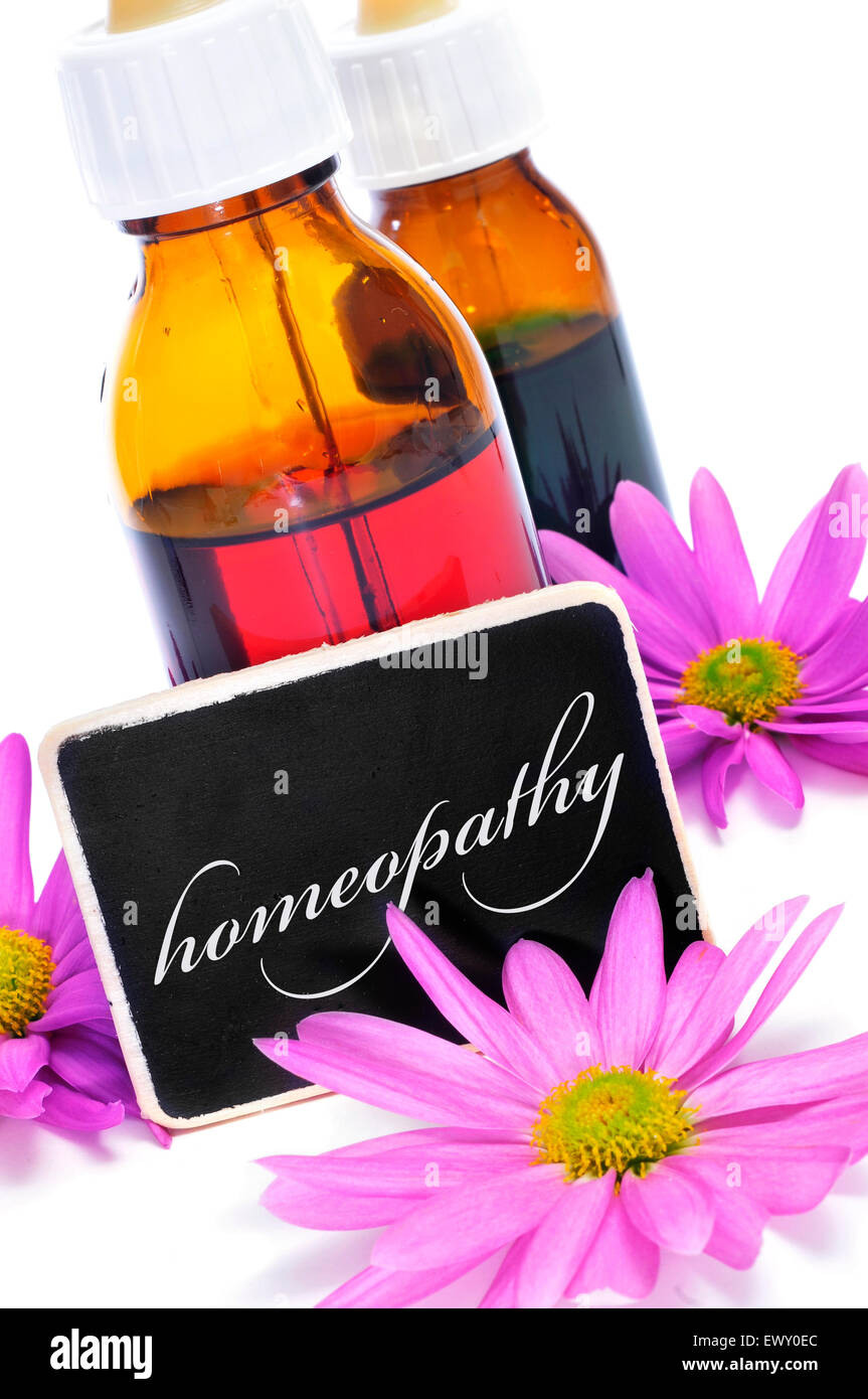 some dropper bottles and a blackboard with the word homeopathy written on it and pink flowers - Stock Image