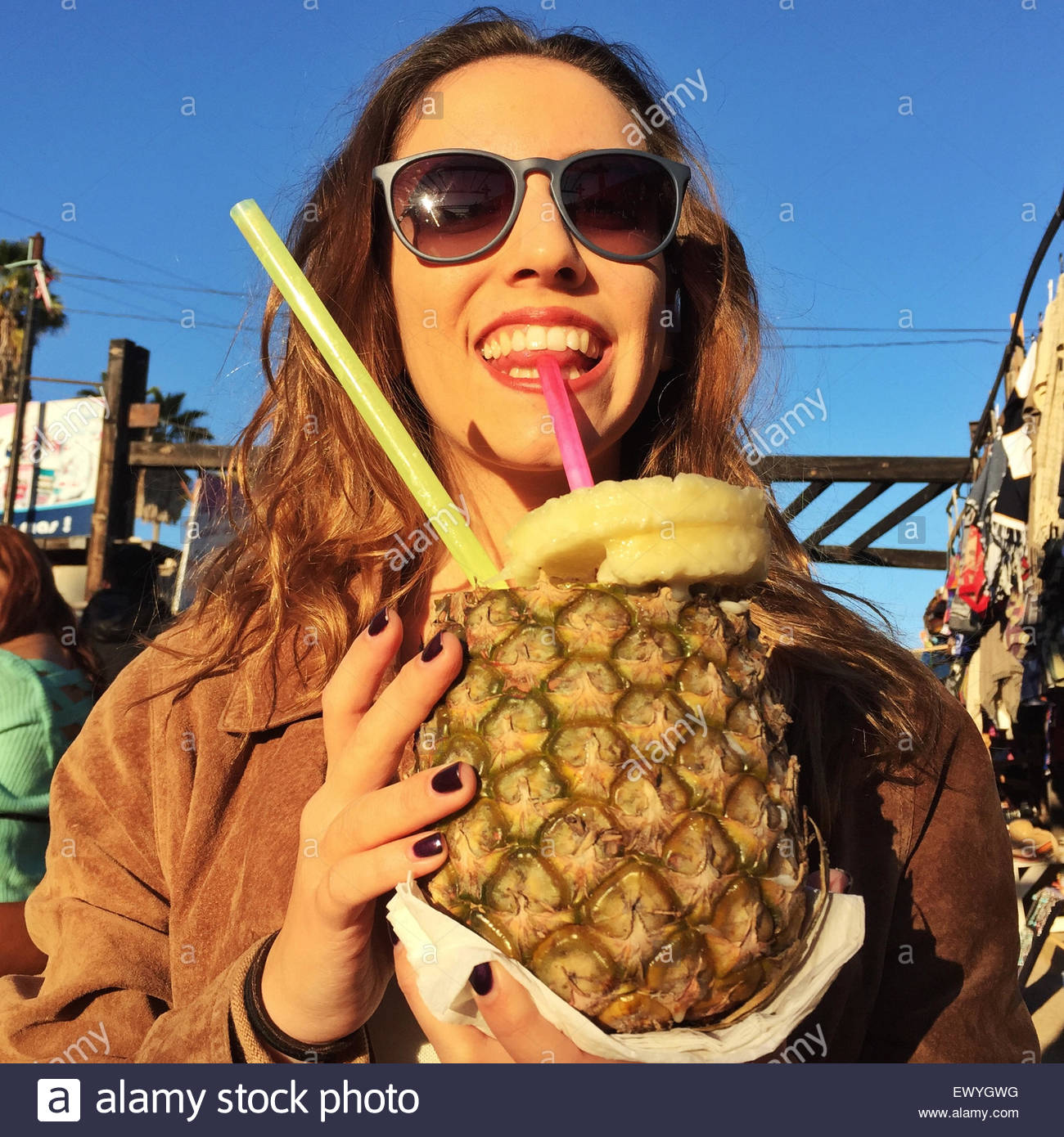 Girl sipping a non alcoholic Pina Colada from a pineapple,  Mexico - Stock Image
