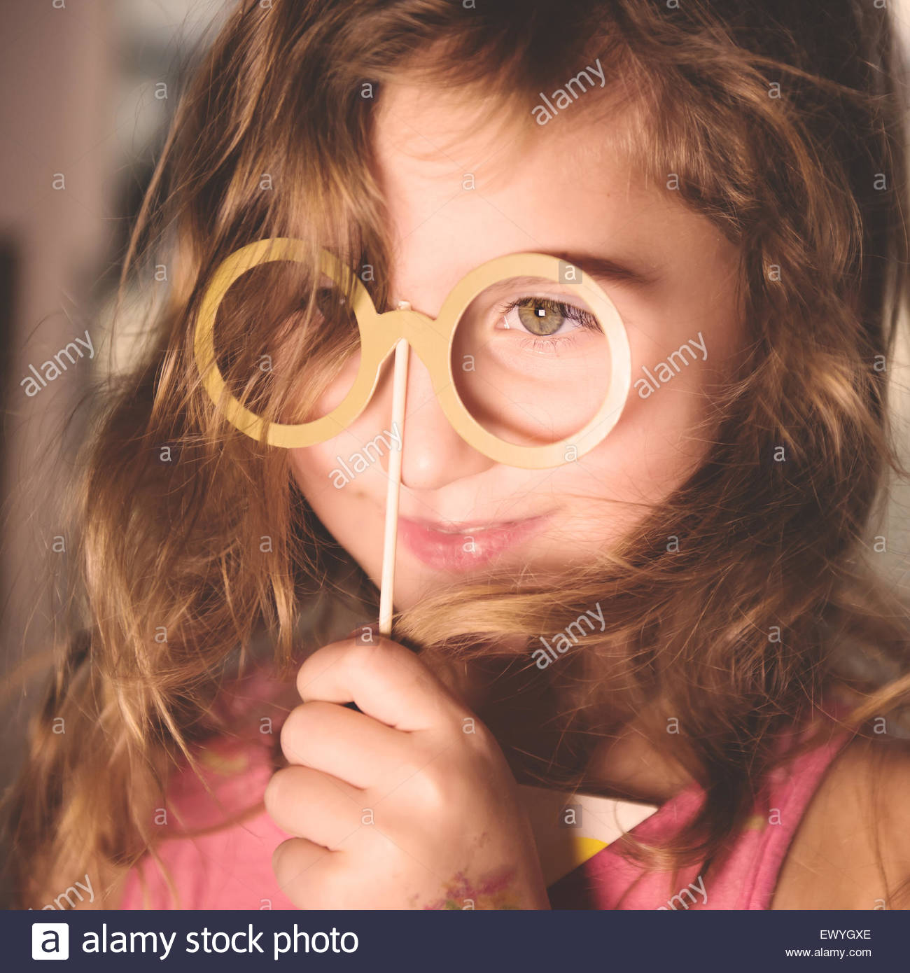 Girl holding party prop glasses on a stick in front of her face - Stock Image