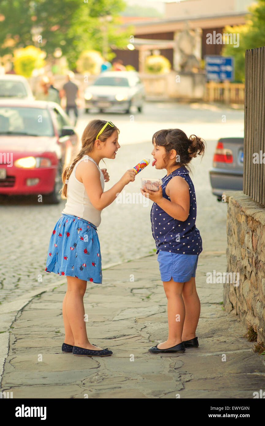 Two girls sharing ice-creams in the street - Stock Image
