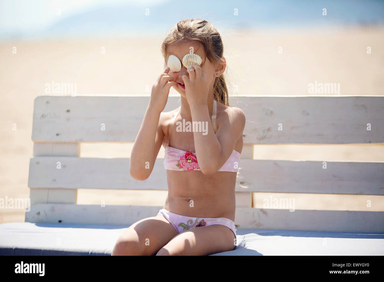 Girl sitting on a bench at the beach holding sea shells in front of her eyes - Stock Image