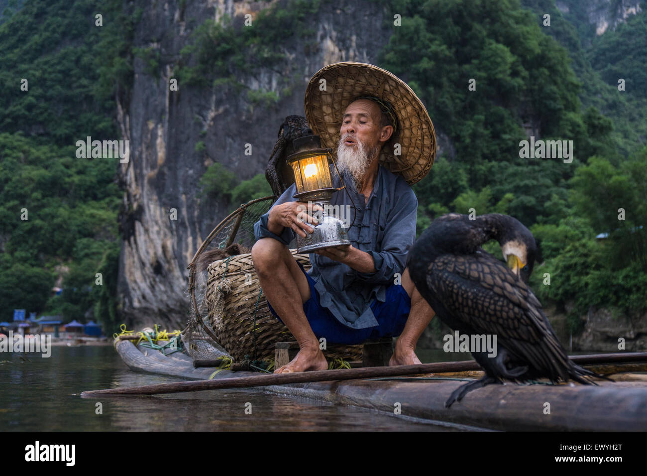 Cormorant fisherman on a raft holding a lantern, Guilin, China - Stock Image
