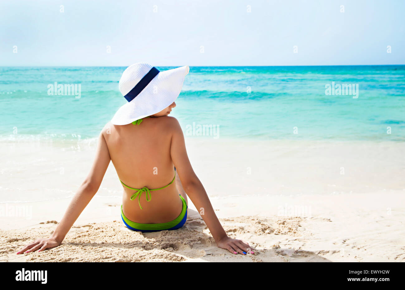 Rear view of a woman sitting on a beach - Stock Image