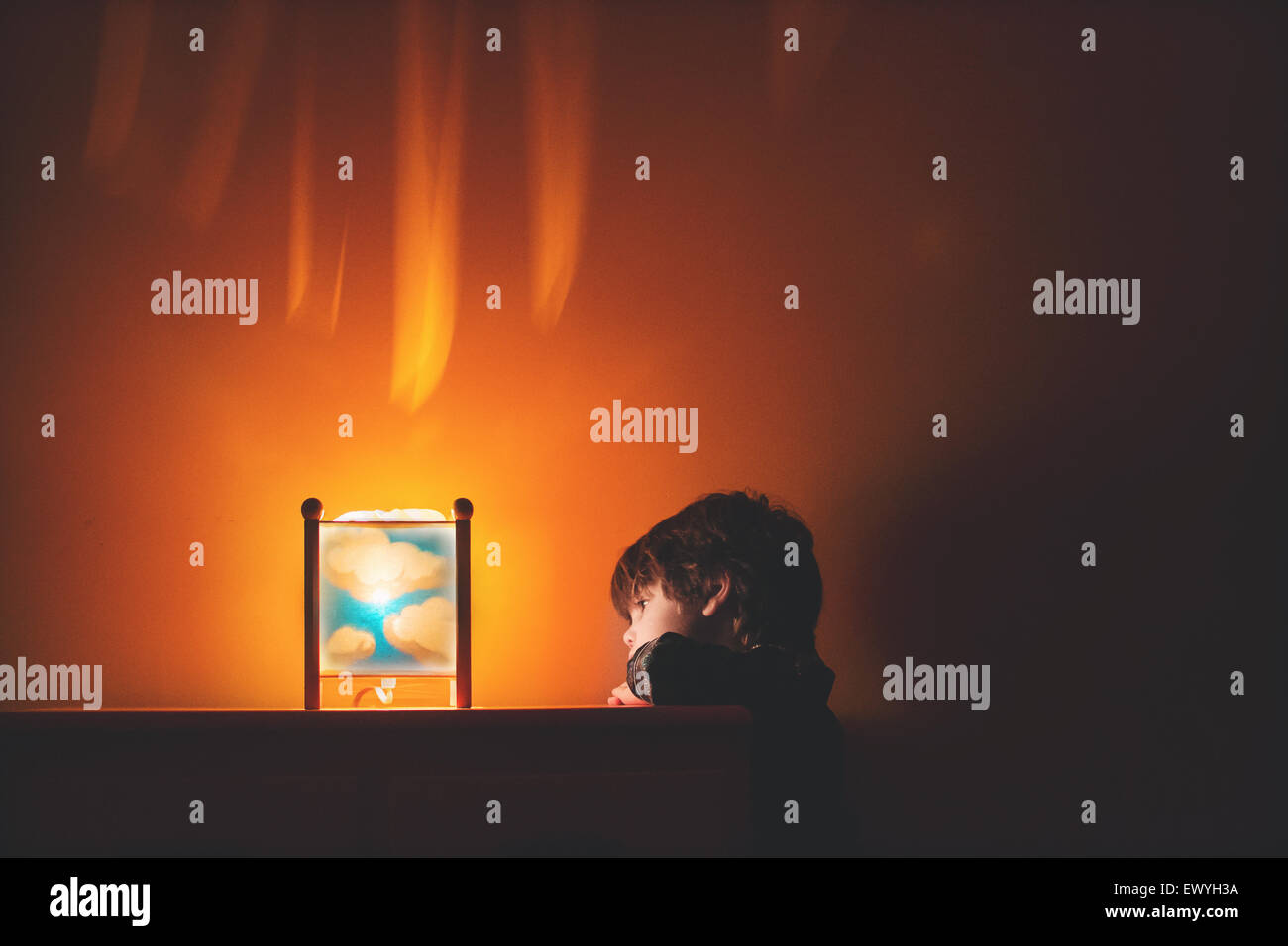 Young boy looking at cloud nightlight - Stock Image