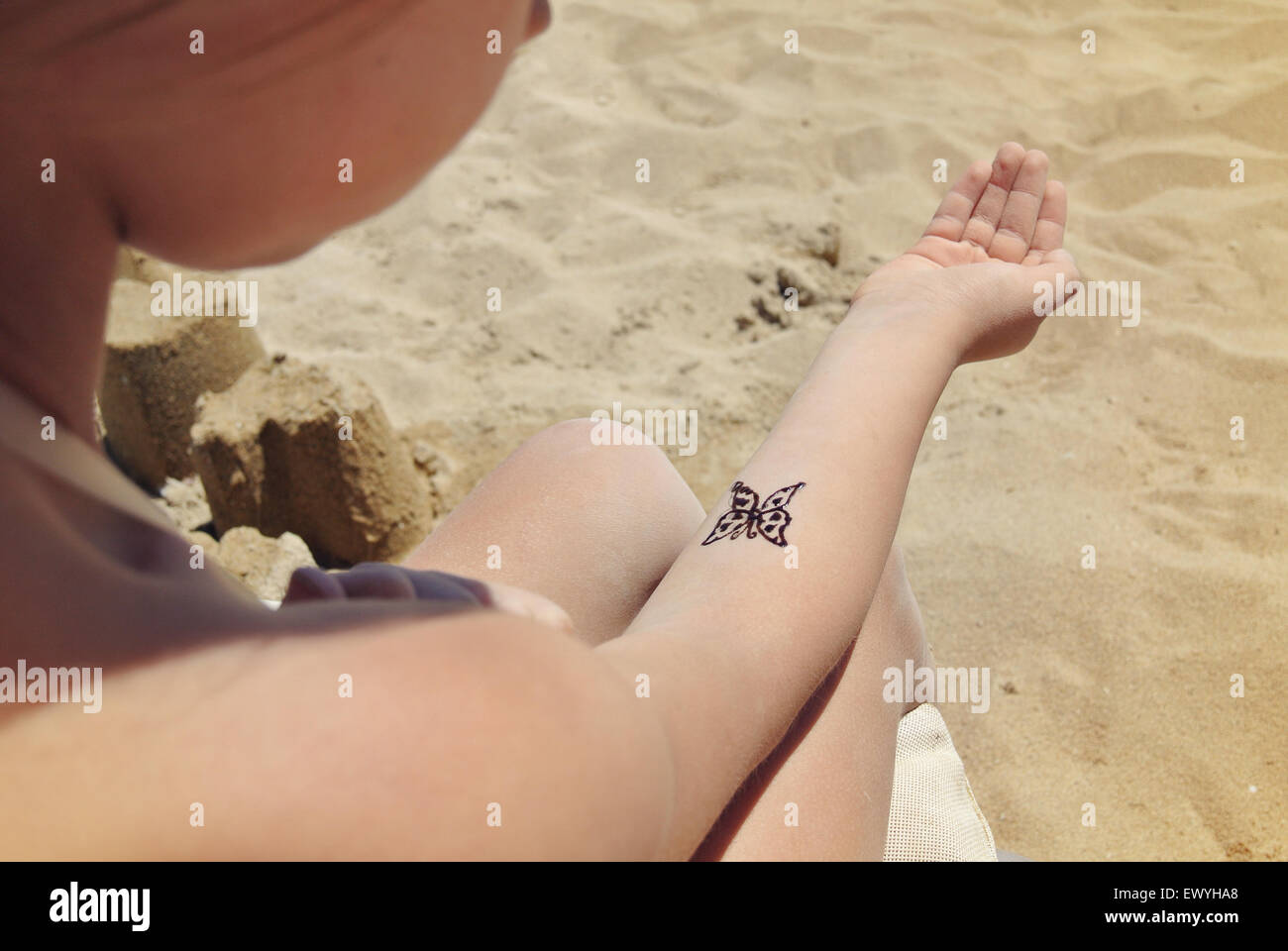 Girl on the beach with a temporary butterfly tattoo on her arm - Stock Image