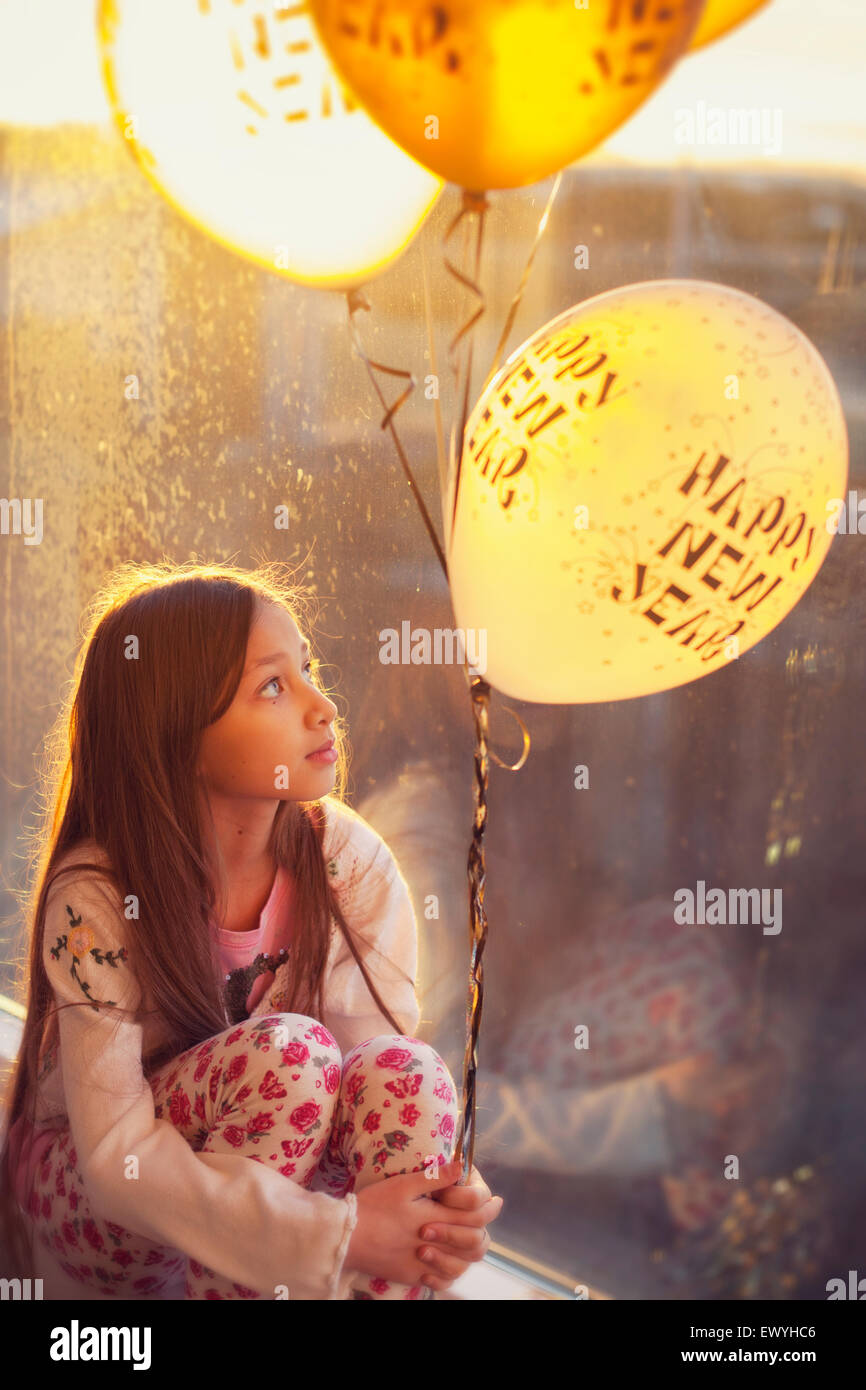 Girl sitting by a window Holding New Years Eve Balloons - Stock Image