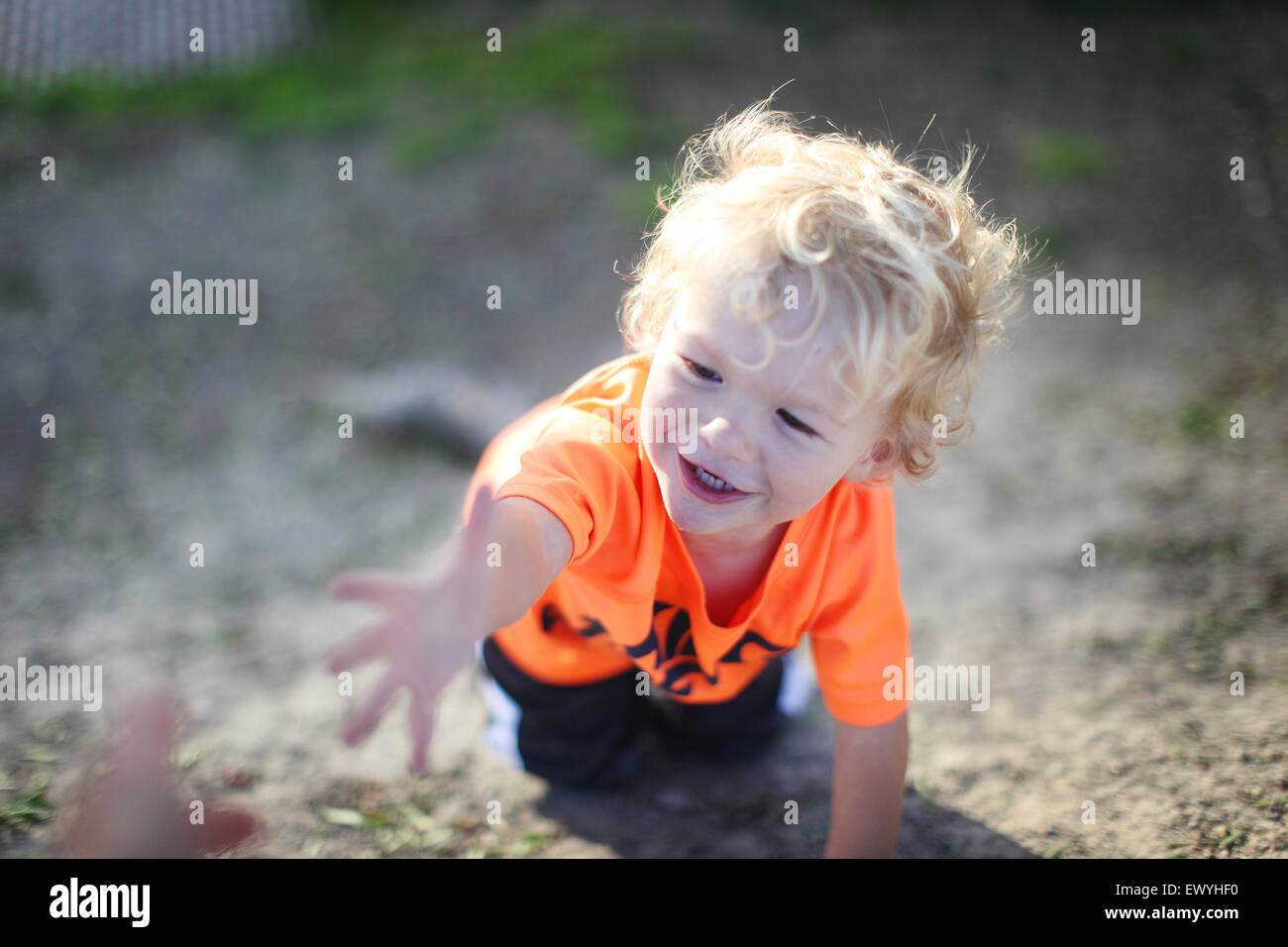 Smiling boy on all fours reaching for a hand - Stock Image