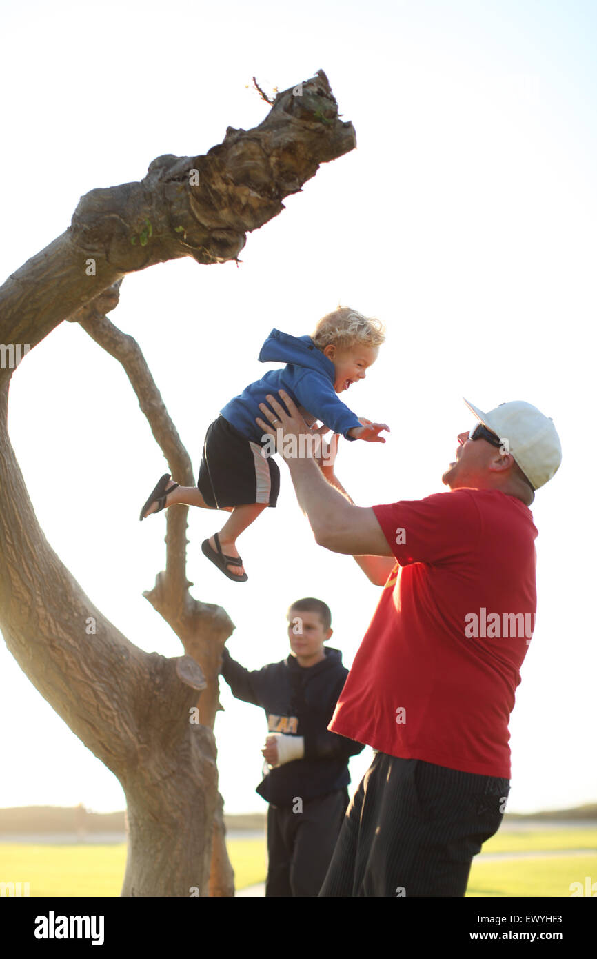 Father catching son jumping off a tree trunk with boy in background - Stock Image