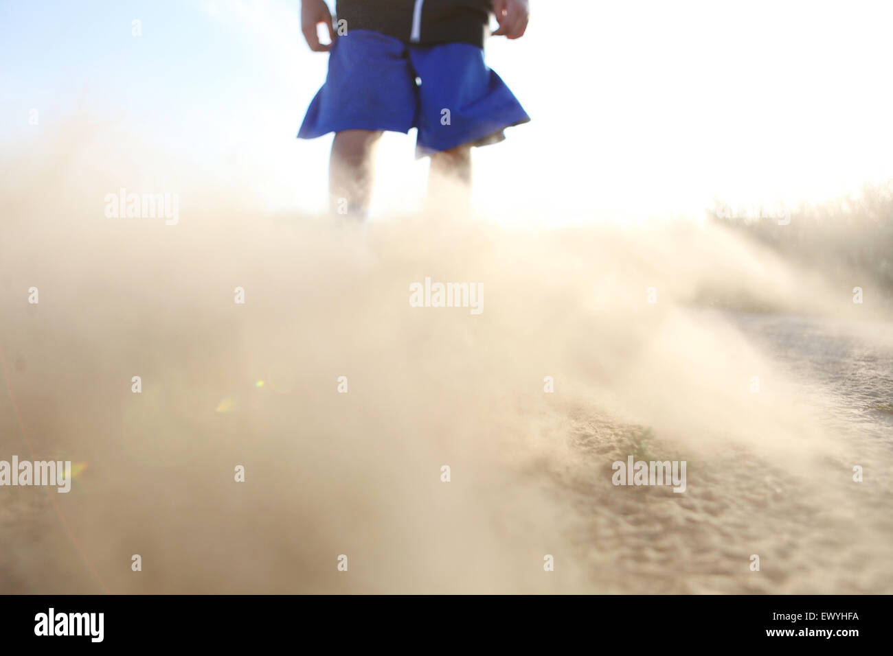 Low angle view of a boy in shorts with sand blowing - Stock Image