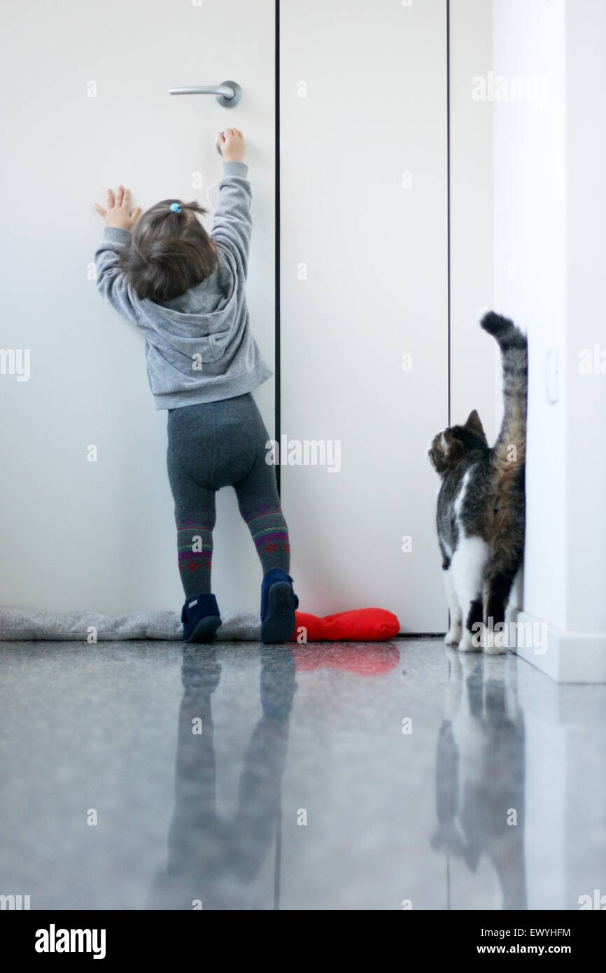 Baby girl trying to open the door for her cat - Stock Image
