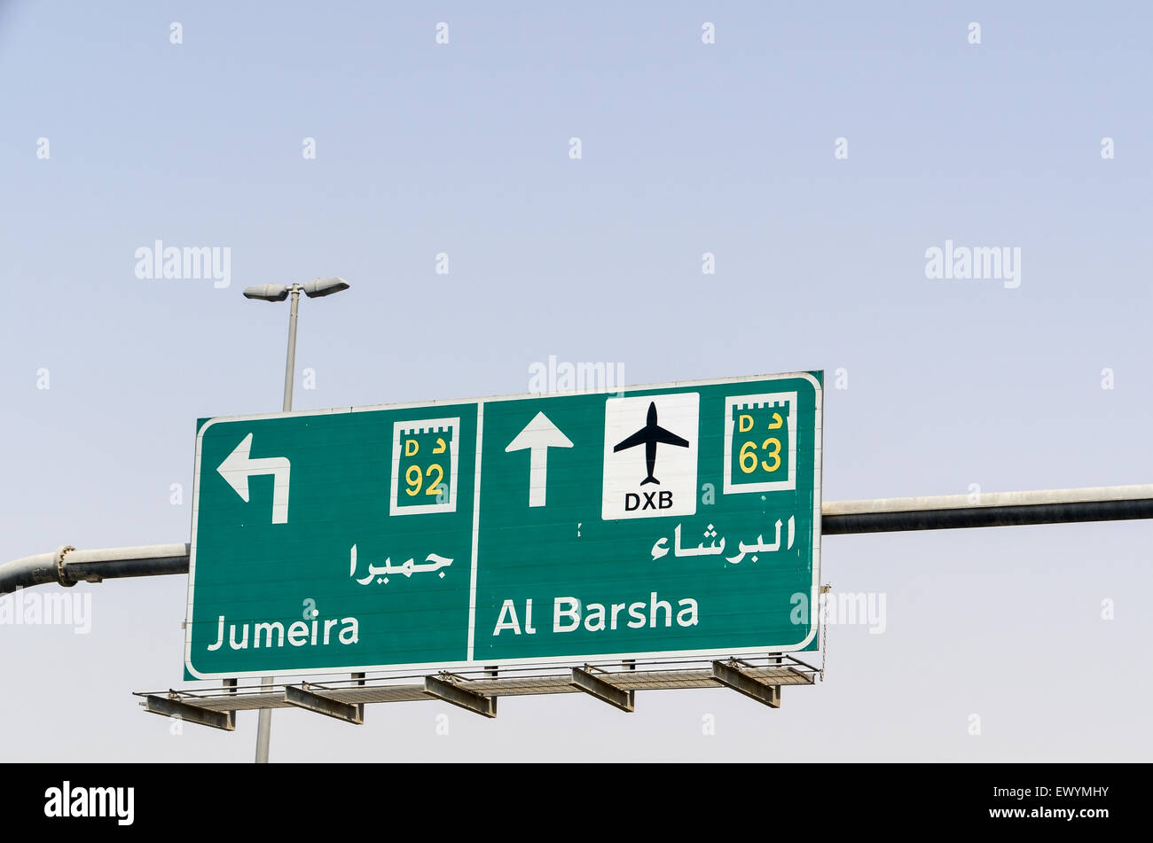 Road sign in Dubai, UAE, indicating Jumeira and Al Barsha, with the DXB airport logo - Stock Image