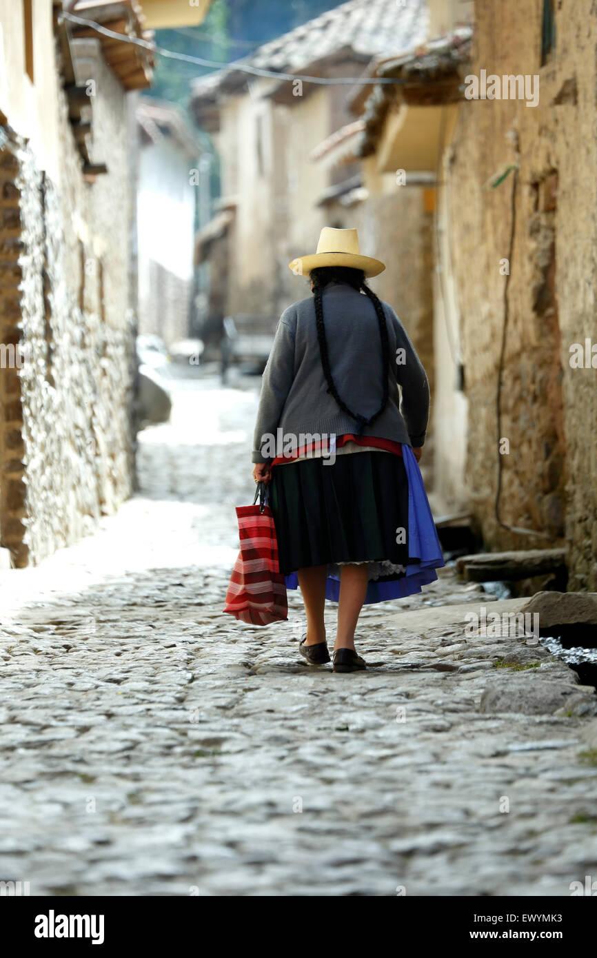 Quechua woman walking down the street, Ollantaytambo, Cusco, Peru - Stock Image