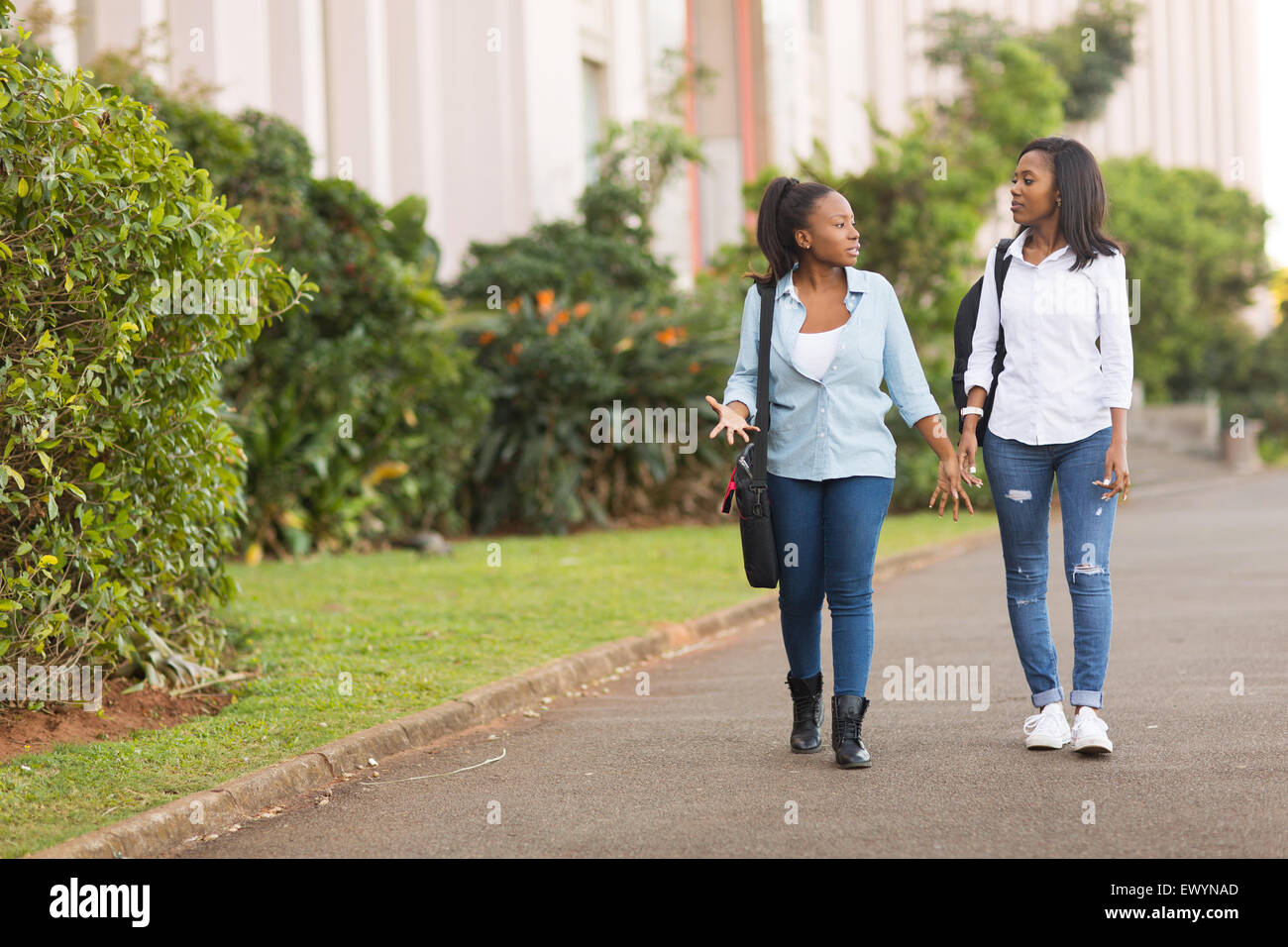 pretty African college students walking together on campus Stock