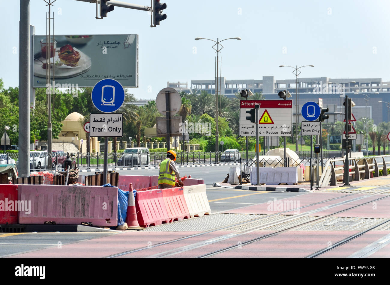 Migrant construction workers working in the middle of the road in Dubai, UAE - Stock Image