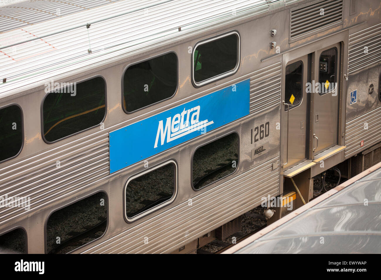 A Metra train car with a Metra sign sits in a station in Chicago, Illinois. - Stock Image