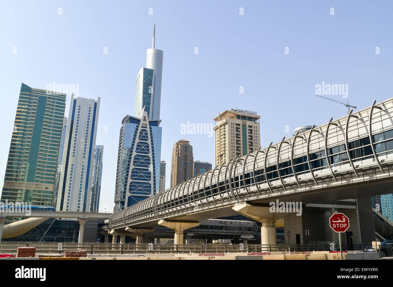 STOP sign, Jumeirah Lake Towers, near Dubai Marina, UAE, and bridge over the highway to the metro station - Stock Image
