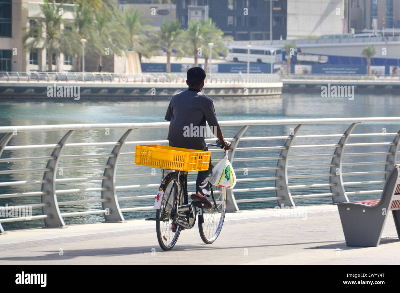 Immigrant worker cycling on the empty promenade of the Dubai Marina early morning - Stock Image