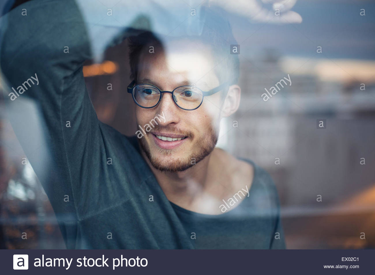Young man looking out of window - Stock Image