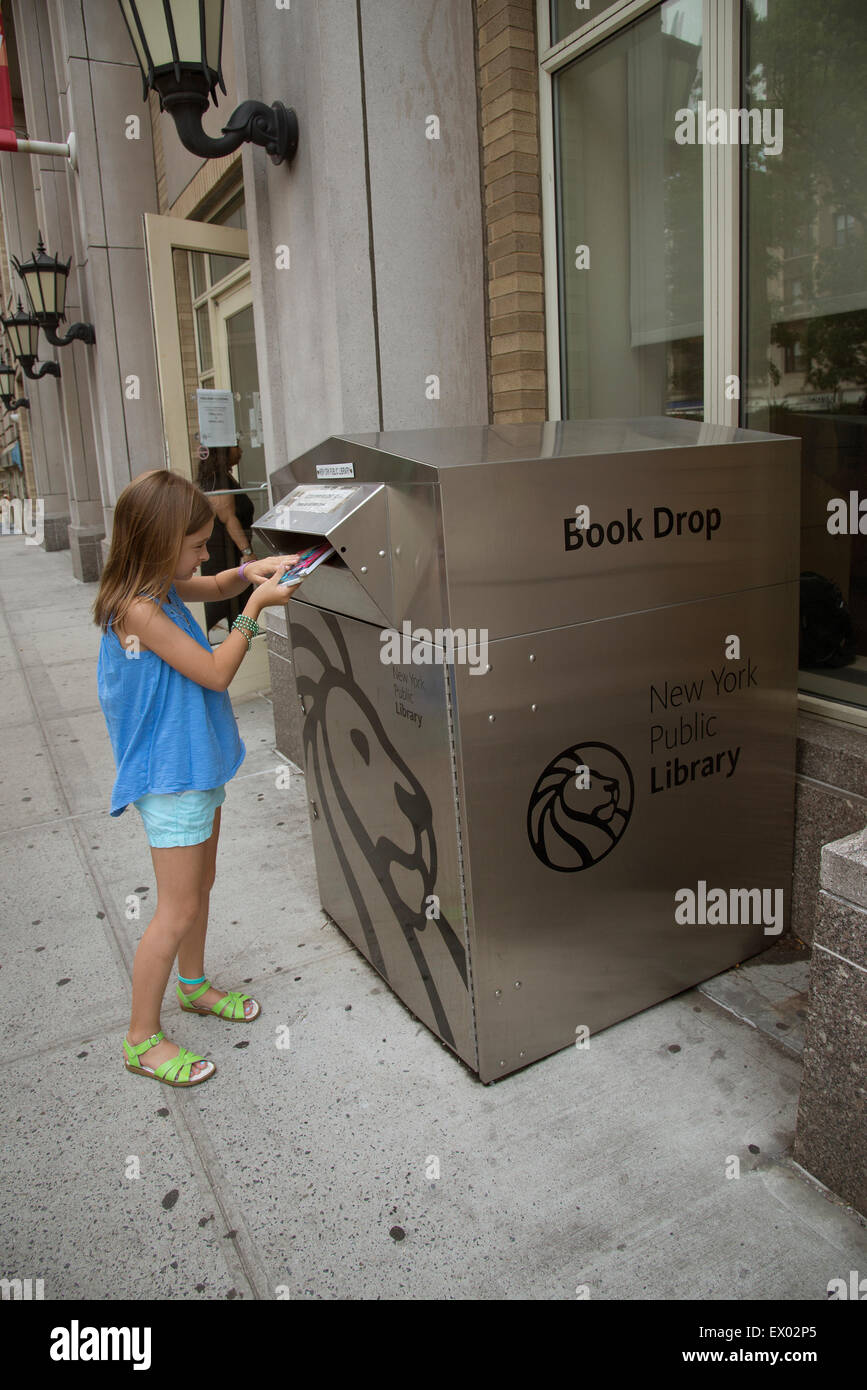New York Public Library book drop young child returning the books she has read - Stock Image