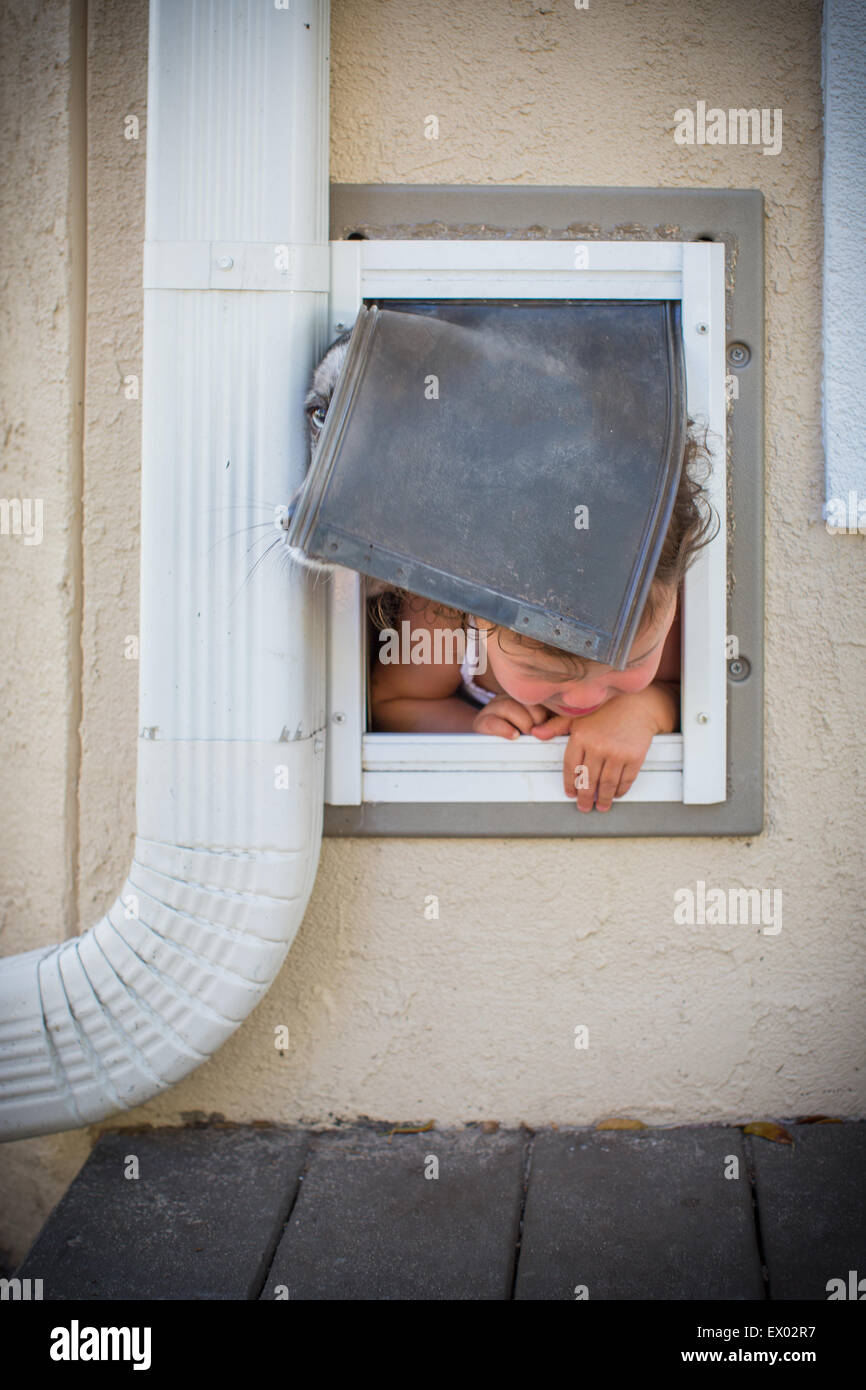 Toddler and dog escaping through doggy door - Stock Image