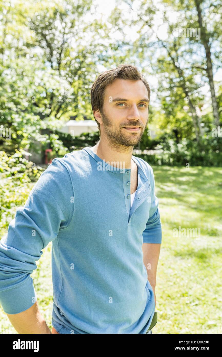 Portrait of confident mid adult man in garden - Stock Image