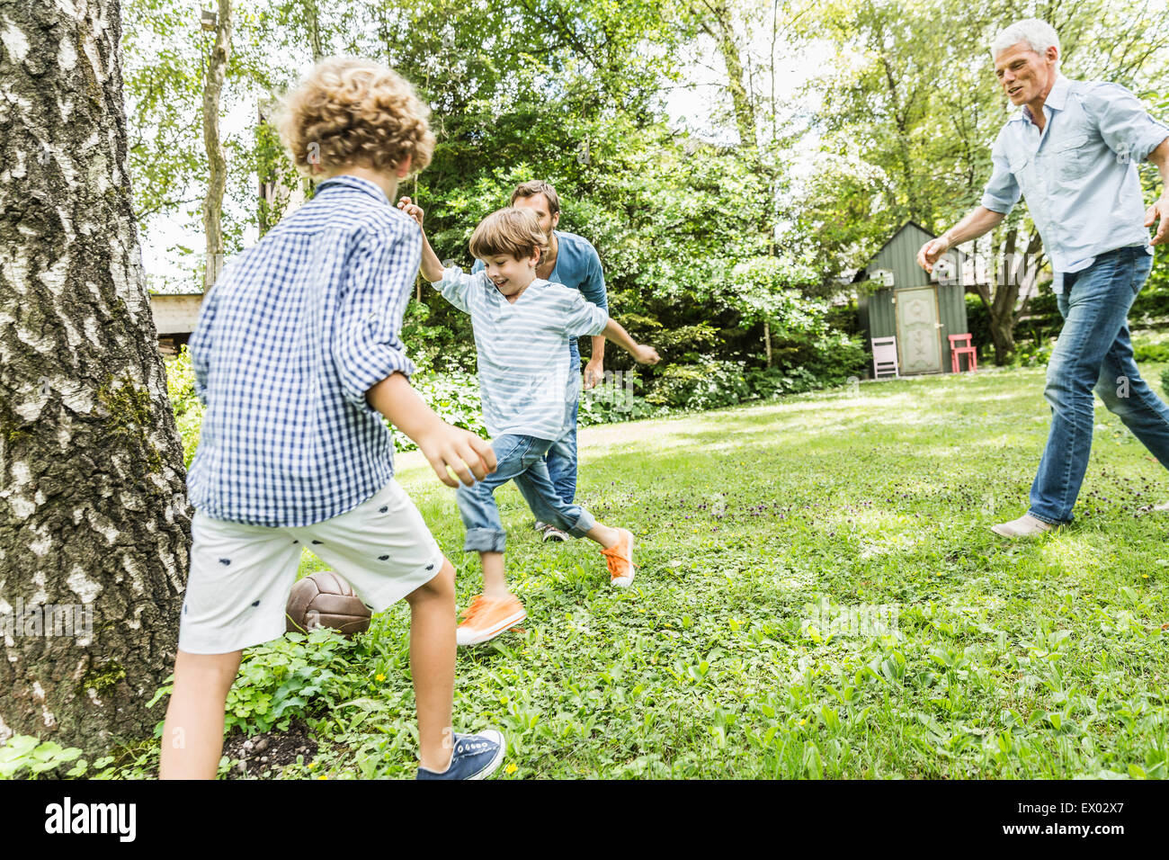 Mid adult man and father playing garden soccer with sons - Stock Image