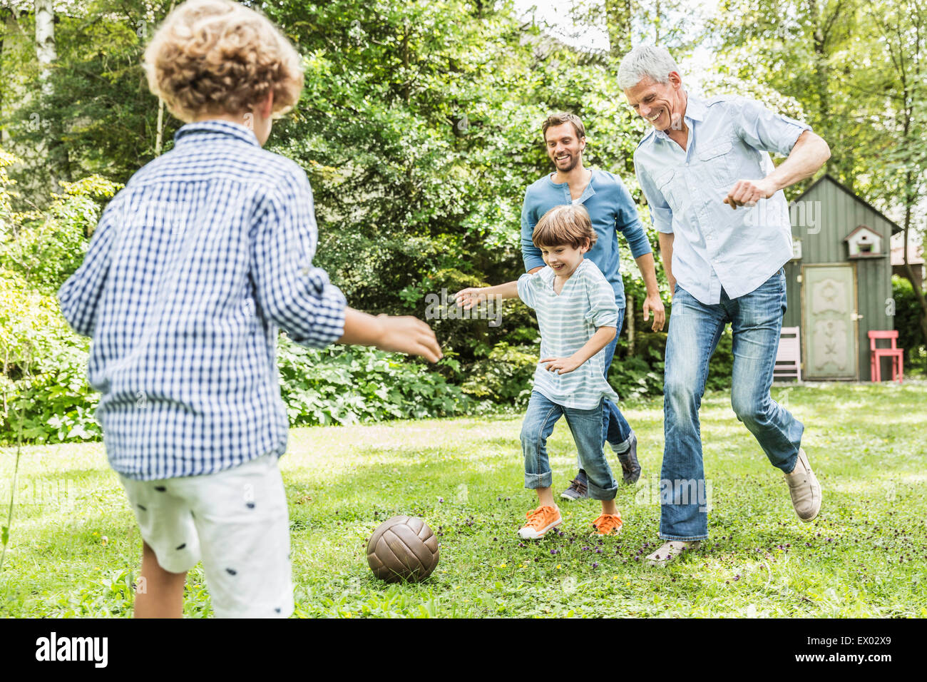 Mid adult man with father and sons playing garden soccer - Stock Image