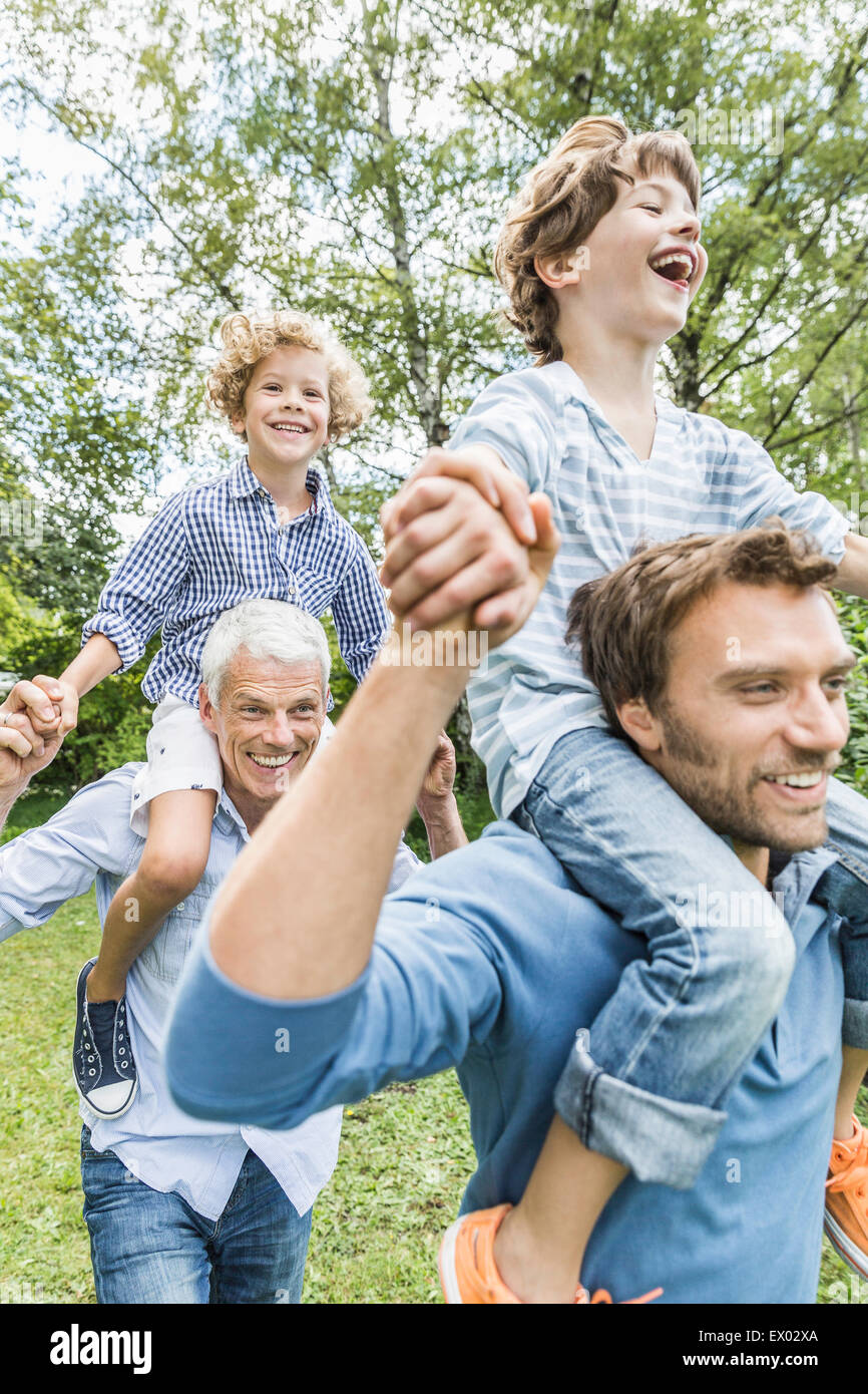 Mid adult man with father giving sons shoulder carry in garden Stock Photo