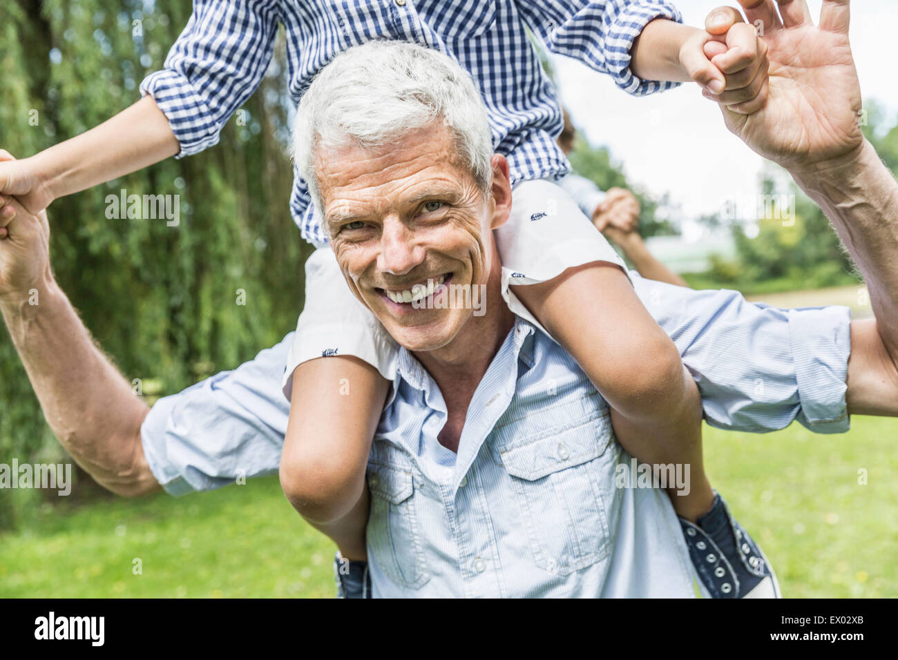 Portrait of grandfather giving shoulder carry to grandson in garden - Stock Image