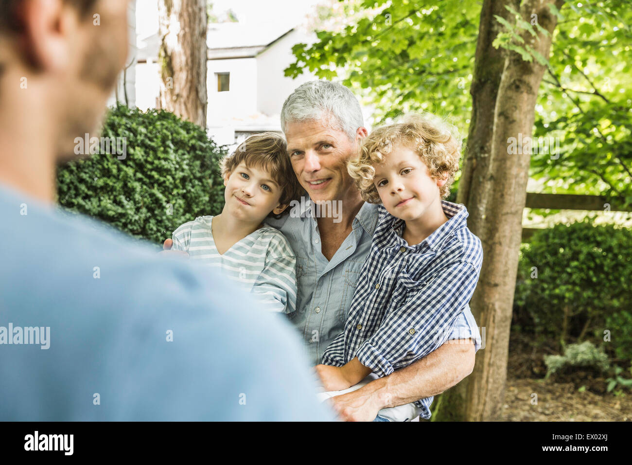 Mid adult man with father and sons in garden - Stock Image