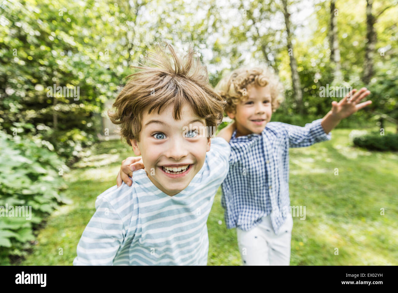 Two brothers running in garden - Stock Image